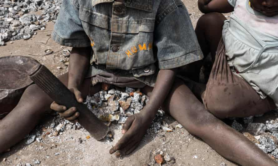 A young boy crushes stones in a quarry in Ouagadougou, the capital of Burkina Faso, where adults and children work
