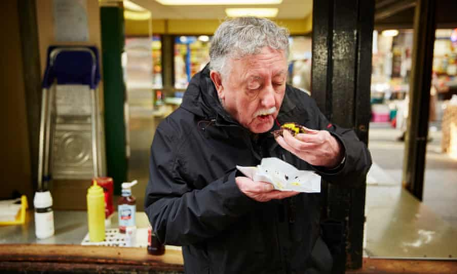 A customer eating black pudding from Chadwick's, who have been making from a secret recipe for the last 150 years.