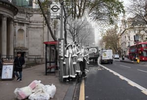 Men dressed as Santa Claus wait for a bus in December 1960. Commuters wait at the same bus stop in Holborn on 24 November 2017