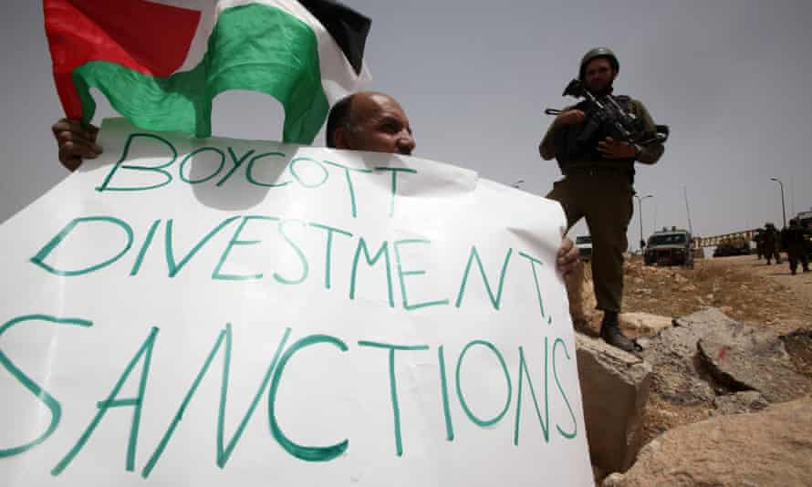 """A file photo taken on June 8, 2013 shows a Palestinian holding a placard which """"Boycott divestment, sanctions"""" as part of a protest in the West Bank village of Surif, west of Hebron."""