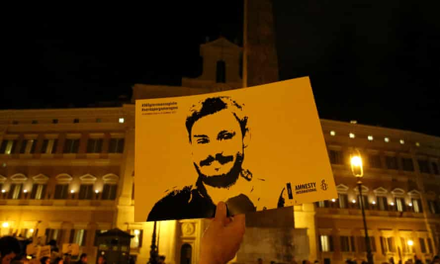 A man holding a sign depicting Giulio Regeni during a vigil in Rome.