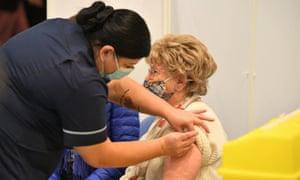 Woman receives the Oxford/AstraZeneca Covid-19 vaccine in Surrey, UK.