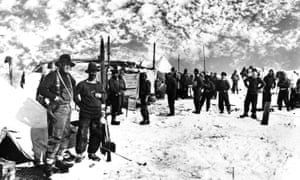 group of about 30 men in snowy landscape with makeshift camp