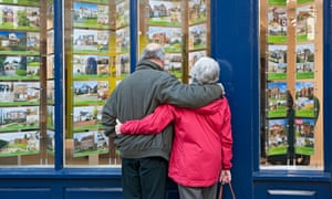 Older couple looking in estate agent's window