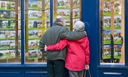 An elderly couple look into an estate agent window