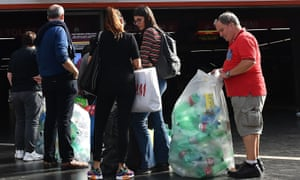 Italians take plastic bottles to a reverse vending machine at a metro station in Rome.