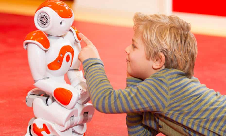 Young child playing with robot at school