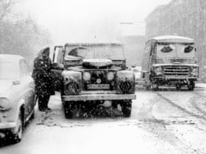 An AA worker in a Land Rover helps a motorist during a blizzard in 1963