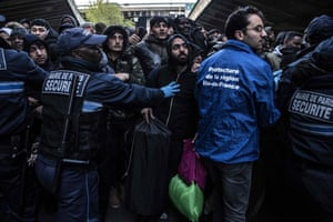 Paris, France: Security agents hold back migrants during the evacuation of a makeshift camp at Porte de la Chapelle in the north of Paris. More than 300 migrants and refugees were evacuated