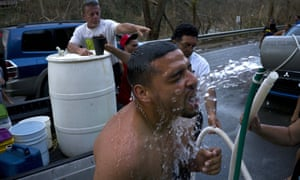 People affected by Hurricane Maria bathe in water piped in from a mountain creek, in Naranjito, Puerto Rico, amid concerns about islanders' exposure to contaminated water.