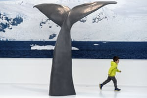 A child runs past a sculpture of a whale's tail in Prémanon, France
