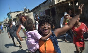 Haitians react to tear gas fired by the police in Port-au-Prince where there were reports of demonstrations, gunshots and burning tires.