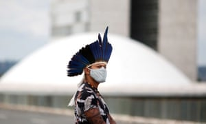 An indigenous man wears a protective mask during a protest against the president Jair Bolsonaro's mining politics regarding indigenous lands, and demanding the Brazilian environment minister Ricardo Salles' resignation, outside the Ministry of the Environment building in Brasilia.