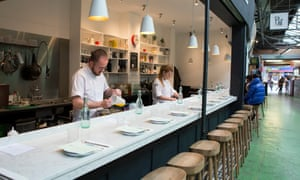 Plot restaurant's long white counter with wooden stools the near side and its two chefs behind