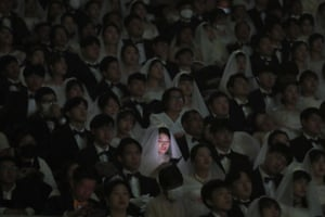 Crowd of brides and grooms, one bride's face lit up by phone screen
