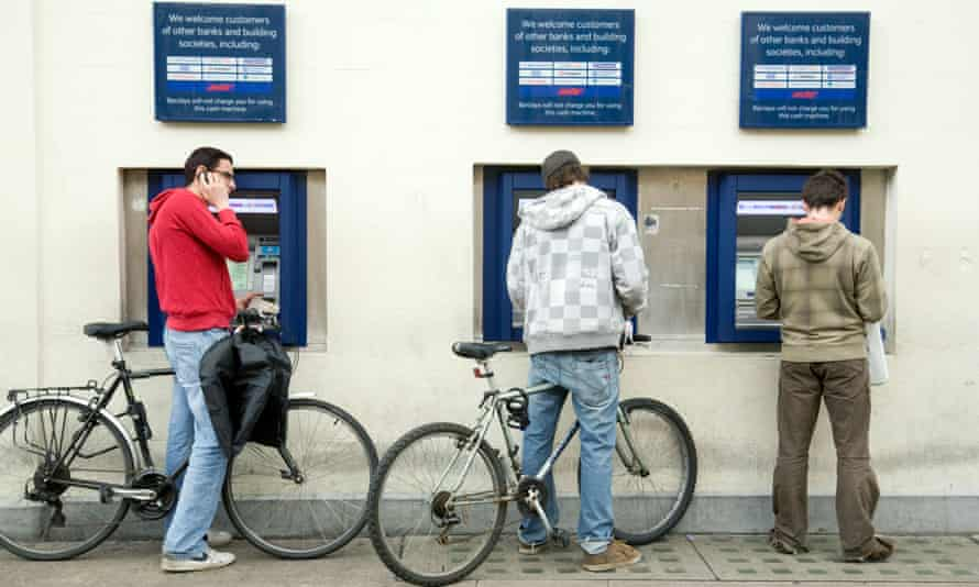 Students using the three Barclays bank ATMs in Market Square, Cambridge.
