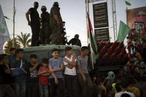 Palestinians gather as Hamas militants parade at a rally just over a week after a cease-fire was reached in an 11-day war between Hamas and Israel.