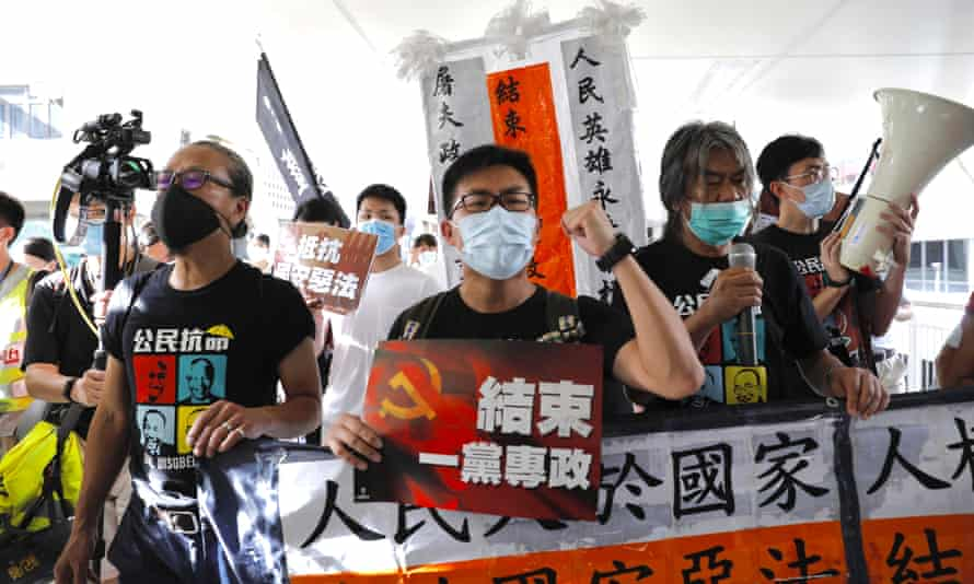 """Pro-democracy protesters shout """"Stop One Party Rolling"""" as they march toward the flag raising ceremony in Hong Kong."""
