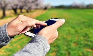 closeup of a young man using a smartphone in a natural landscape, with a grove of almond trees in full bloom in the backgroundFFE8XY closeup of a young man using a smartphone in a natural landscape, with a grove of almond trees in full bloom in the background