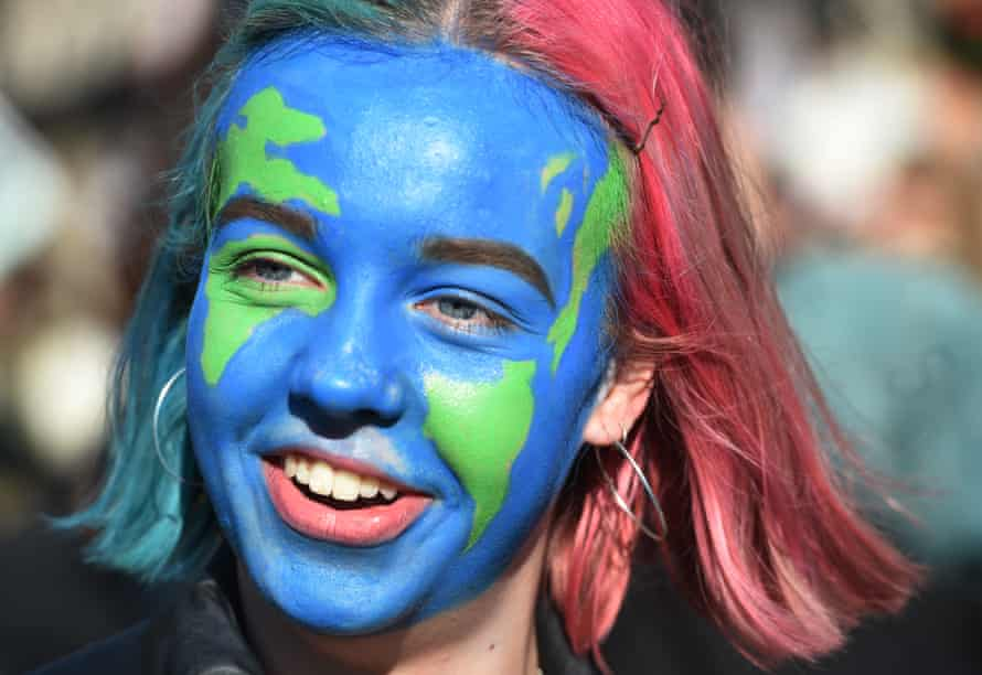 A woman with her face painted to look like the Earth attends the protest