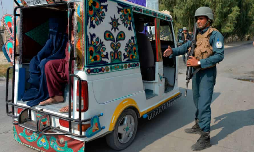 Afghan security forces personnel stop a rickshaw at a checkpoint in Jalalabad