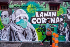 East Java, Indonesia A woman walks past a mural that invite people to fight against the Covid-19, in Surabaya