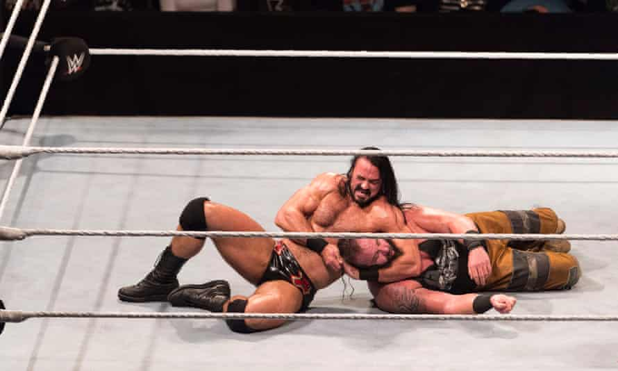 Drew McIntyre holding Braun Strowman in a headlock on the floor of a wrestling ring, Germany, 2018.