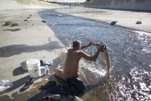 Fernando Lopez bathes and does laundry in the Los Angeles river