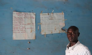 Mohamed Moray, clinical supervisor for Caps, poses before group counseling guidelines adorning the walls of the organisation's office in Kailahun