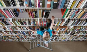 a young reader climbs a stepladder to high bookshelves.