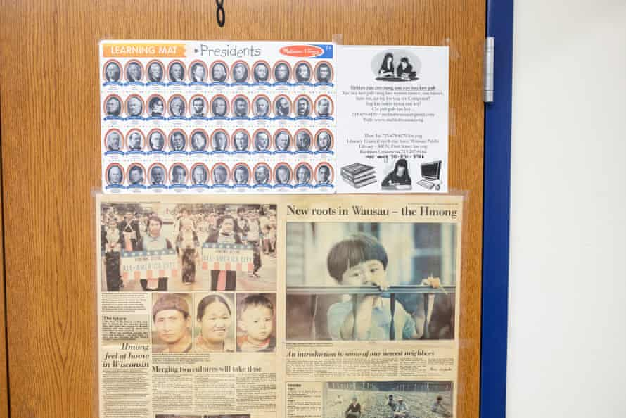 An old newspaper clipping of the Hmong community in Wausau hangs on a door at the Wausau World Market with a presidents of the United States poster.