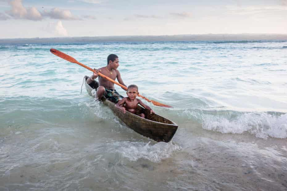 Local children in a canoe on the waves