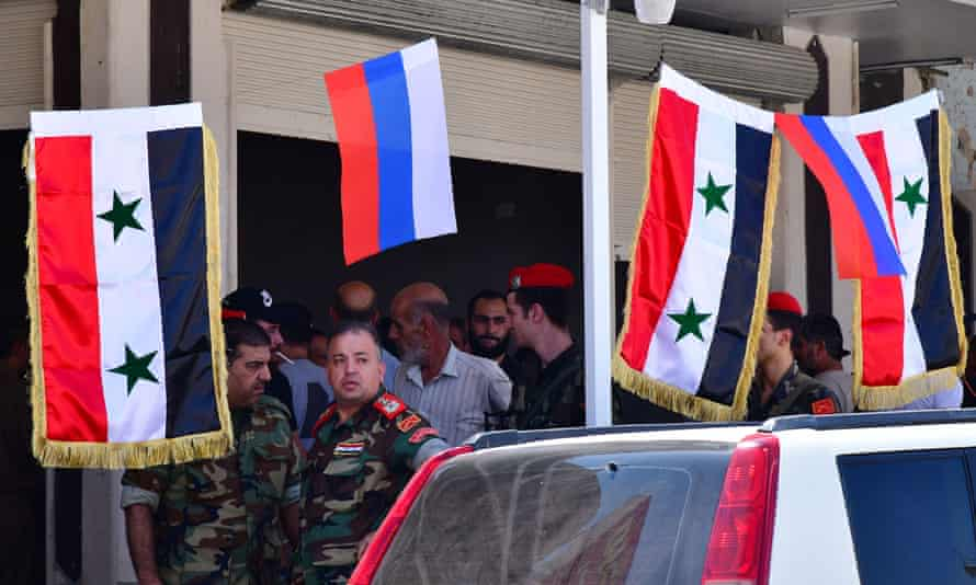 Russian flags sit next to Syrian ones in Daraa province, southern Syria.