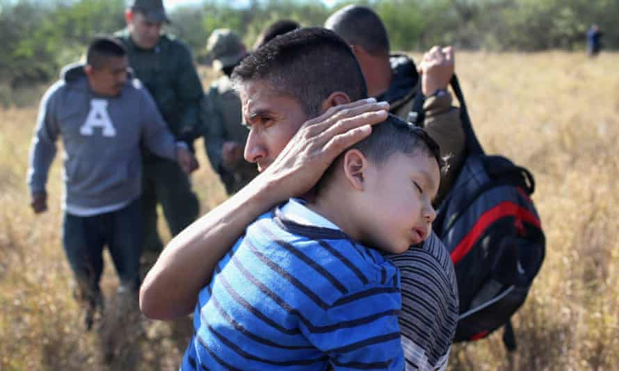 A father holds his sleeping son after they and other undocumented immigrants were detained by border patrol agents on 7 December 2015 near Rio Grande City, Texas.