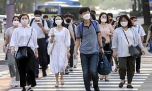 Office workers wearing masks head home after work in Seoul on Wednesday.