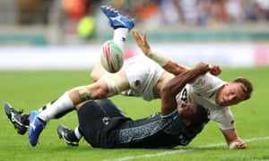 Ben Pinkelman of the USA gets a pass away in a tackle by Paula Dranisinukula of Fiji during the London Sevens at Twickenham.