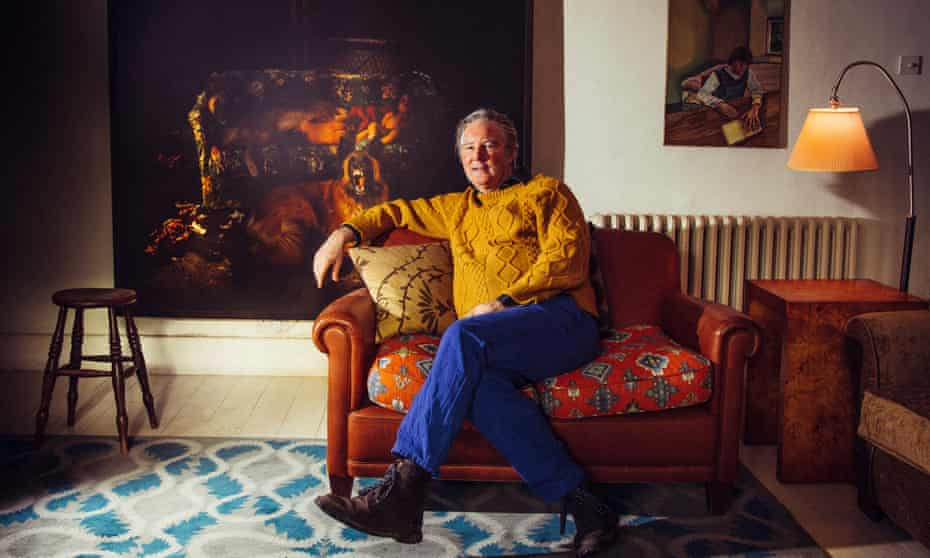Guy Kennaway at his home, wearing bright blue jeans and a mustard-coloured top, leaning back on a sofa with a huge painting behind him