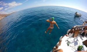 Female swimmer jumps from a boat in the swim, as part of the Minoan Trail swimming trip, in Crete