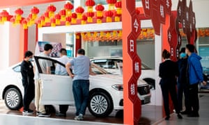 This photo taken on 10 May 2020 shows people looking at Volkswagen cars on display at a showroom in Beijing.