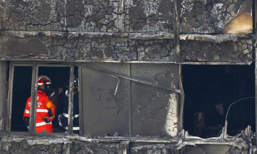 Firefighters survey the damage inside Grenfell Tower.