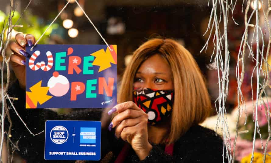 Janet Edwards hangs a festive We're Open sign designed by artist Timothy Hunt in the window of her flower shop in south London to celebrate the American Express Shop Small campaign and welcome shoppers back to the high street as England's second lockdown lifts.