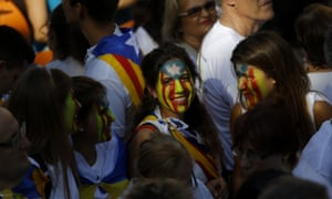 Pro-independence marchers with their faces painted with the Catalan <em>Estelada</em> flag.