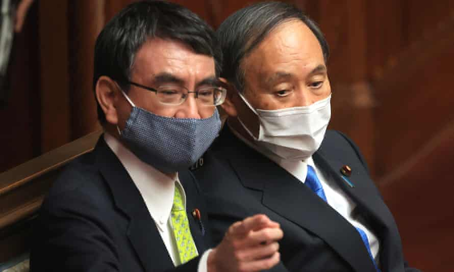 Former PM Yoshihide Suga (R) talks to Taro Kono (L) at lower House's plenary session at the National Diet