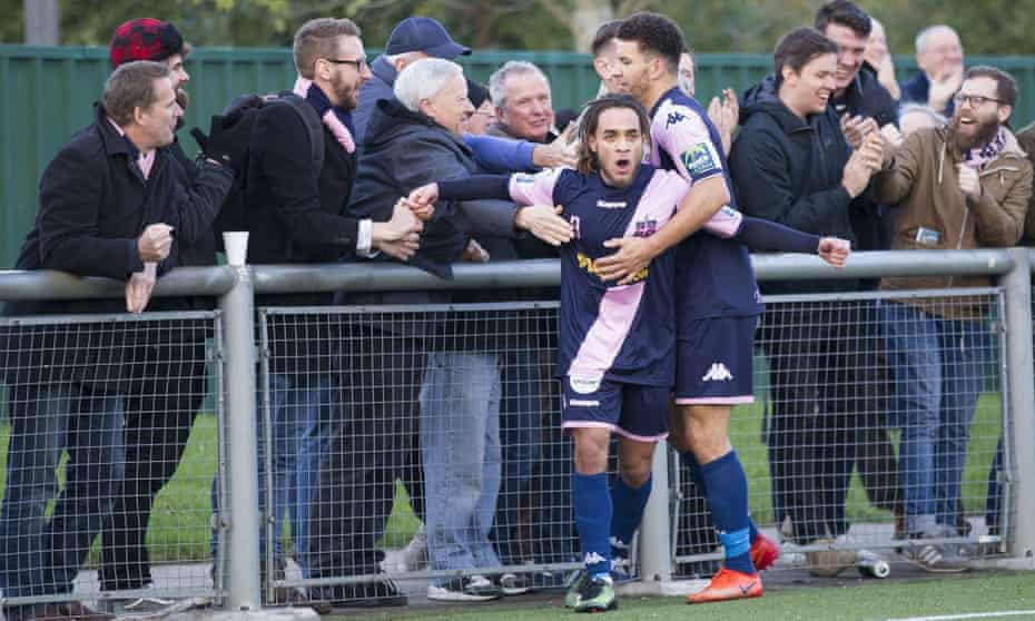Dulwich Hamlet fans embrace striker Reise Allassani after he scores against Harlow Town in November 2017.