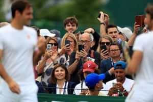 Spectators take pictures of Roger Federer on day nine of the Wimbledon Championships.