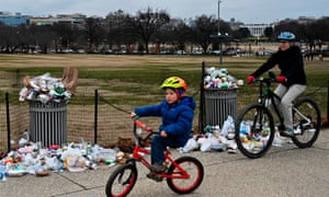 People bike past trash uncollected on the National Mall, due to the partial shutdown of the US government.