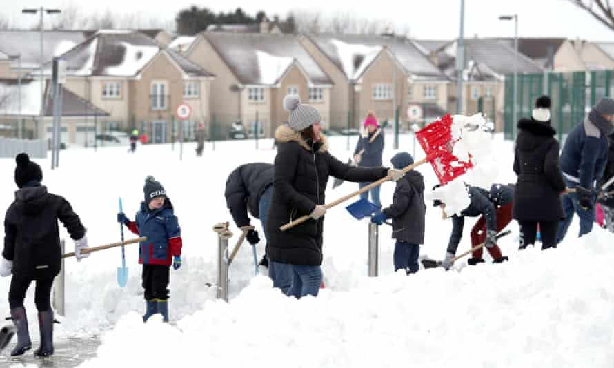 Community volunteers in Larbert, Scotland clear snow from a primary school.