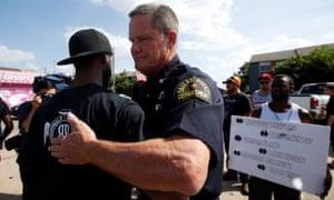 Difficult conversation … a Dallas police officer hugs a man after a Black Lives Matter protest following the shootings in Dallas.