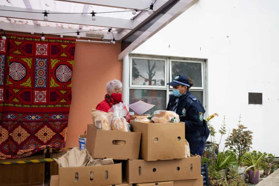 Addi Road volunteer co-ordinator Susan Conyers talks to a police officer among relief groceries.