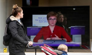 A member of the public walking a shop in Edinburgh with a screen in the window showing Nicola Sturgeon addressing the Scottish parliament yesterday.